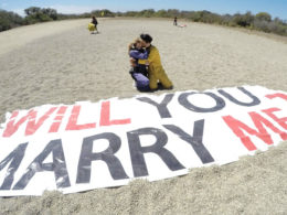couple on beach next to Will You Marry Me sign